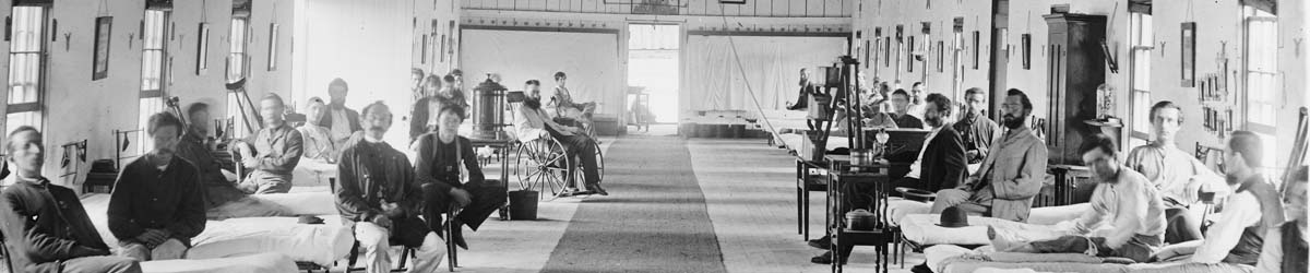 A detail of a photograph taken at the Armory K hospital in Washington, DC during the Civil War. Patients stare out from their beds, seats, and wheel chairs at the camera. Courtesy of the Library of Congress.