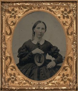 Woman wearing mourning brooch and displaying framed image of a soldier, Courtesy of the LOC
