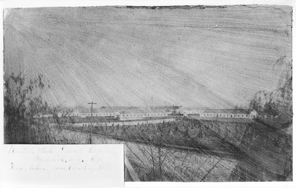 Figure 1: Print of the hospital complex taken from Mount Olivet Cemetery, ca. 1865-7, possibly the work of Frederick artist Jacob Byerly (1807-83). The frame hospital ward buildings are (l-r), M, F, N, K, and O (which is perpendicular to the rest). The stone Barracks buildings and frame kitchen can be seen behind the wards. The fence line is visible in front of the wards, running perpendicular to S. Market Street. View looking northeast. Courtesy of Frederick C. Gaede