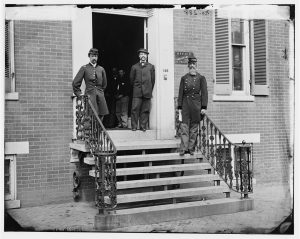 Gen. William Hoffman (at right), Commissary General of Prisons, and staff on the steps of his office, F Street at 20th Street, NW, Washington, DC, 1865. Courtesy of the Library of Congress