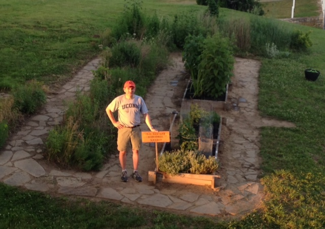 Greg standing in front of the garden after a season of hard work.