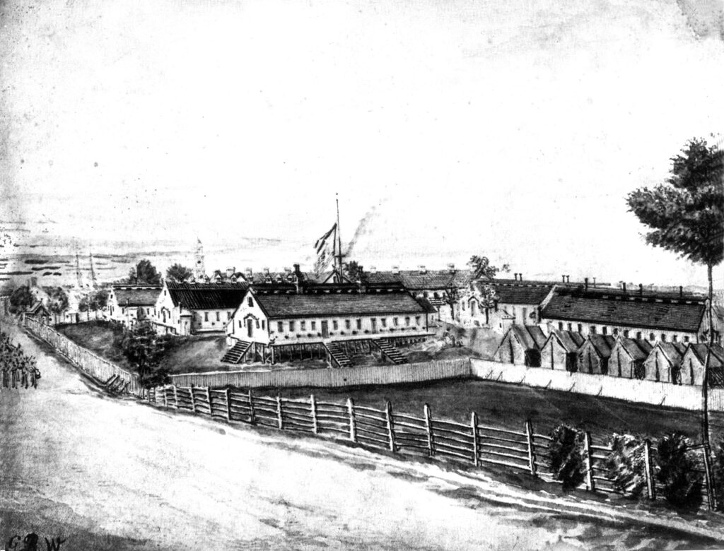 Figure 2: General Hospital #1, Frederick, undated drawing, most likely 1865. The stone barracks (with multiple chimneys) can be seen in the center behind the frame buildings. The ward buildings, from left to right, are Ward M, Ward F, Ward N, Ward K, and Ward O. The tents are included in the fenced enclosure. View from the southwest.